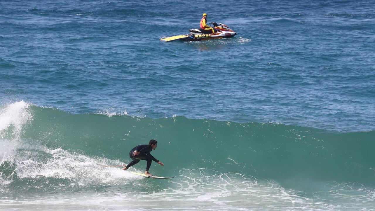 A surfer rides a wave at Burleigh as a lifesaver patrols on a jet ski. Picture: Jason O'Brien
