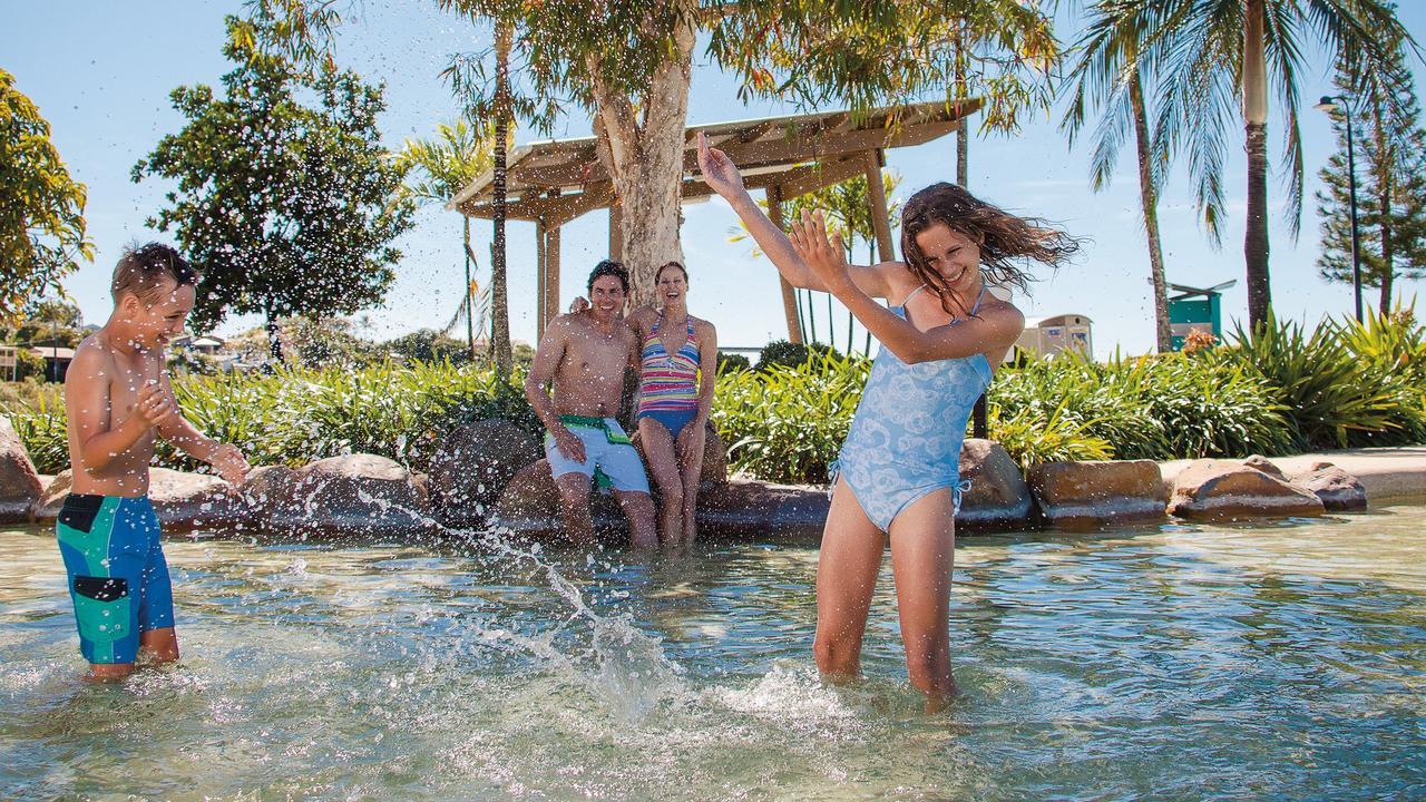 A family enjoys splashing around in the waters at the Airlie Beach Lagoon. Photo: Tourism Whitsundays
