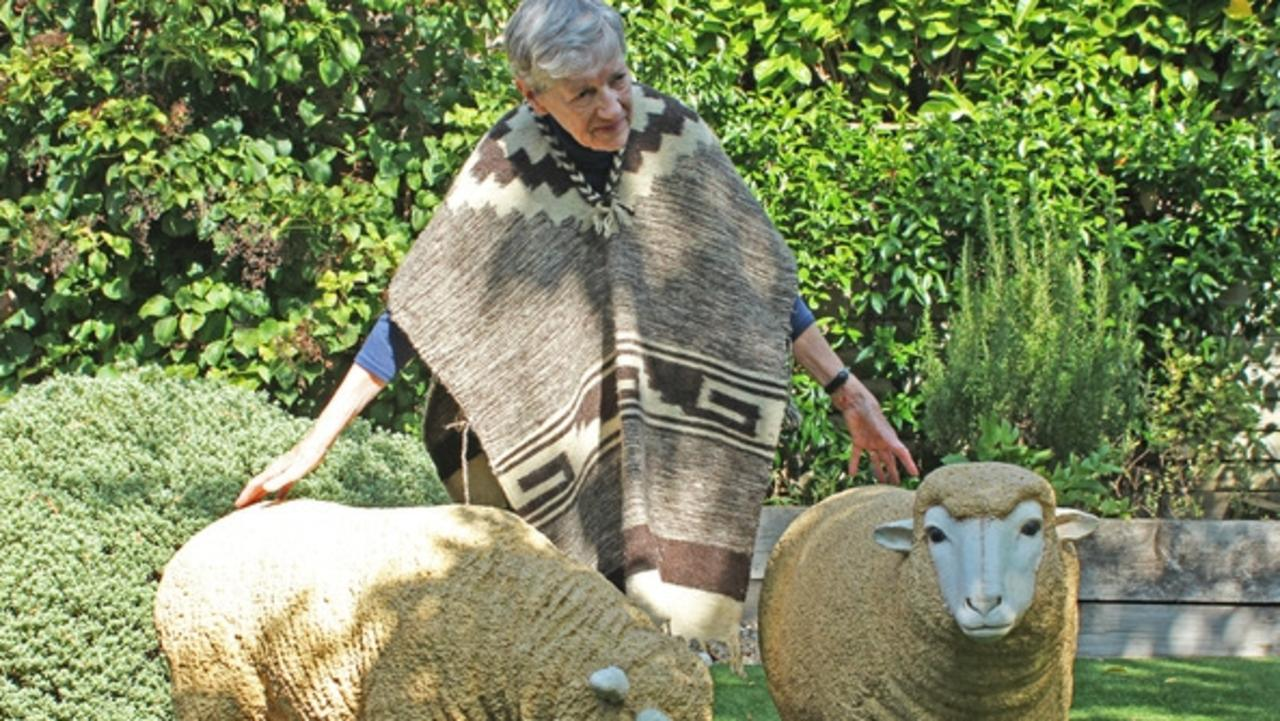Palm Cove resident Mary Watson, 84, with garden sheep statues in a bid to come home from the UK. Picture: Supplied