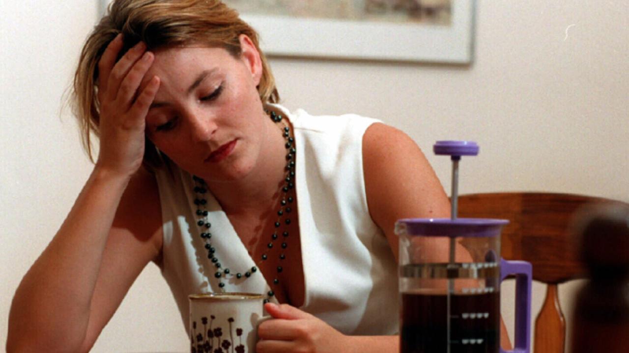 Stressed tired woman drinking mug of coffee.   headache stress women