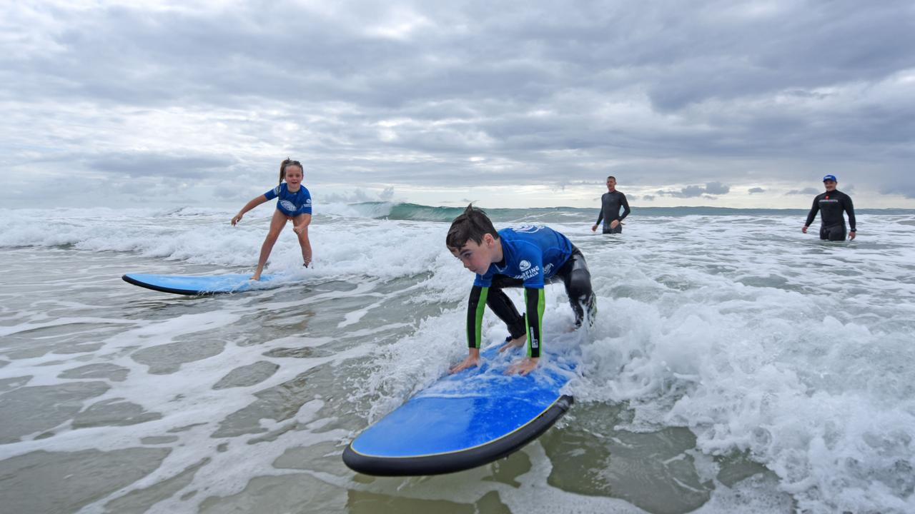 Junior surfers catch waves at Broadbeach during the Surfing Australia Surf Groms session. Picture: Supplied