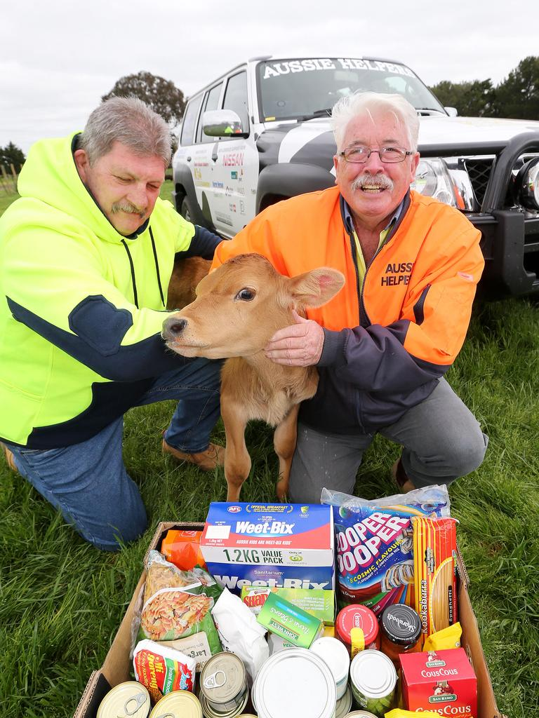 Aussie Helpers John Mc Donald and Brian Egan holding one of the food hampers they distribute to dairy farmers with Whisky the calf. Picture: Mike Dugdale