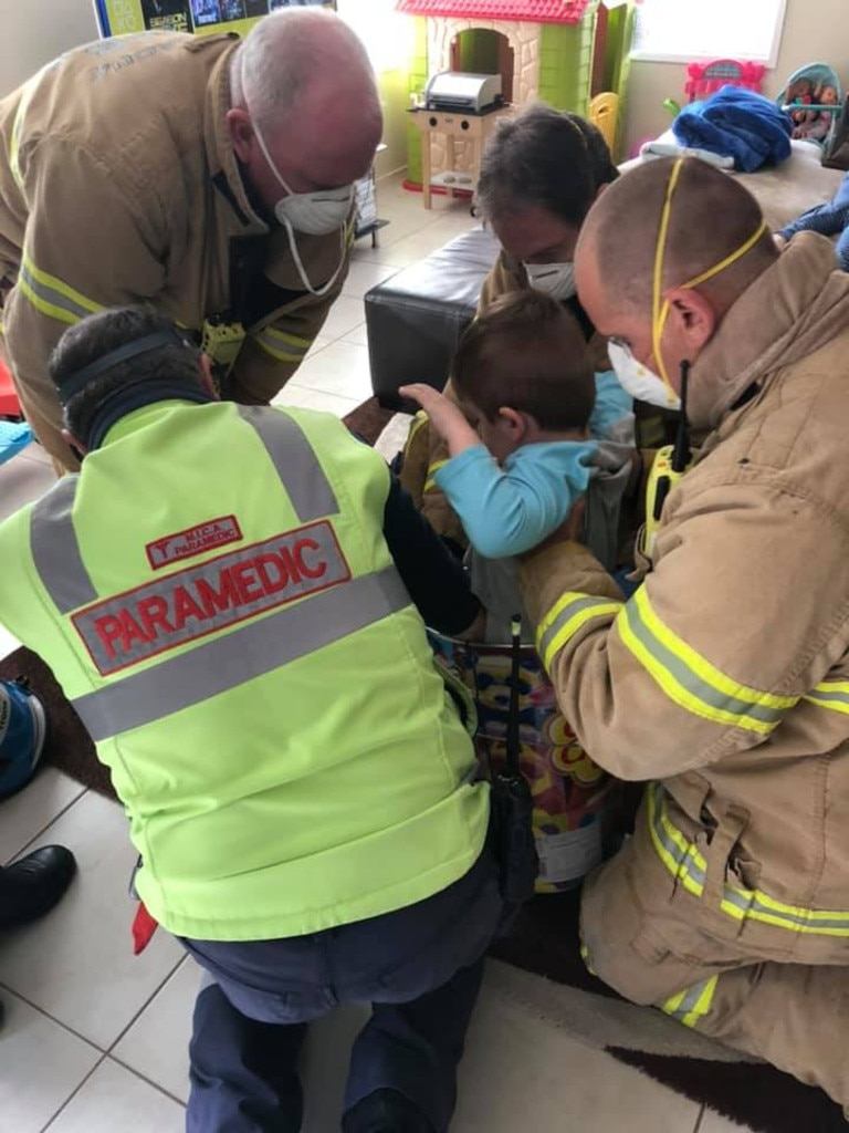 Firefighters work to rescue Alessio from a Chupa Chups tin. Picture: Facebook/Sheree Caruso