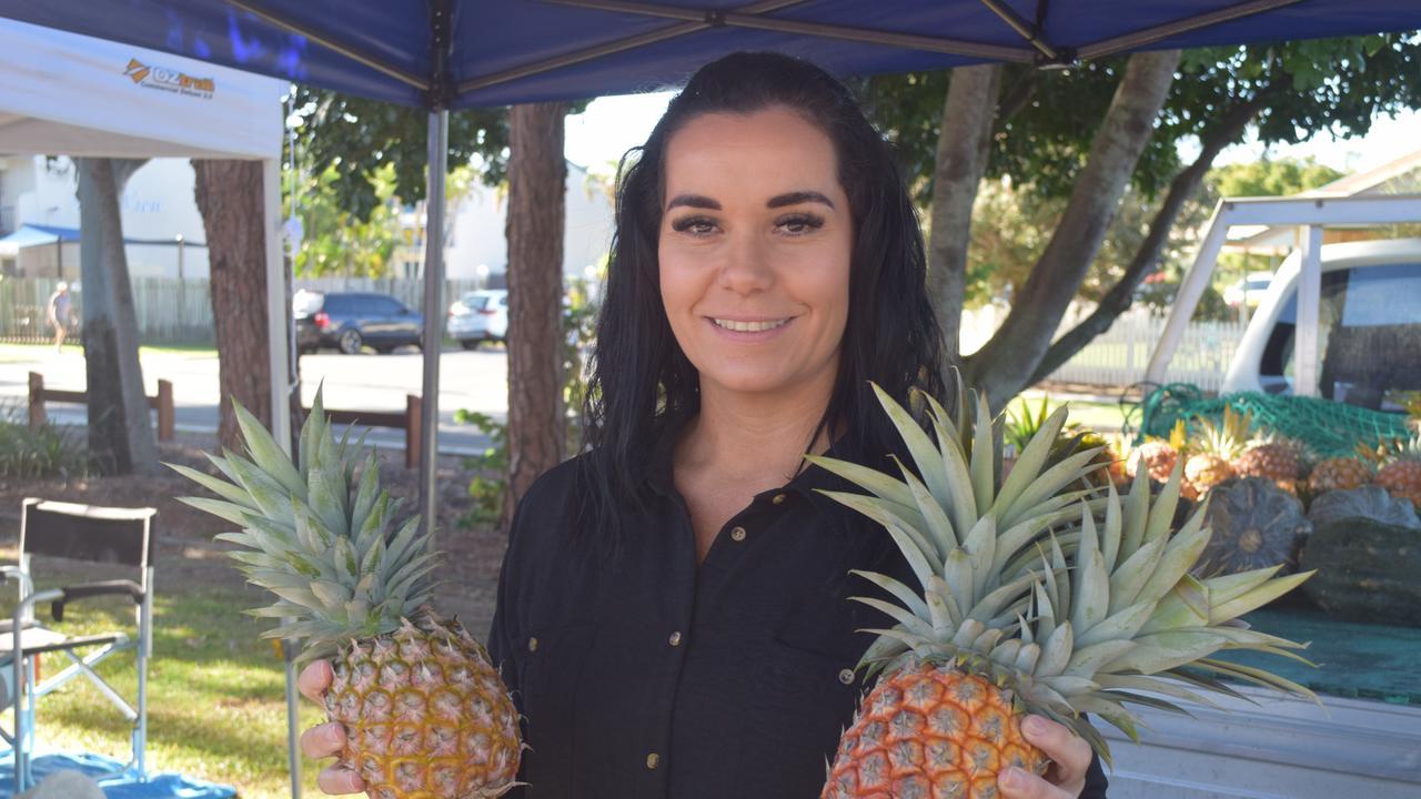 URANGAN PIER MARKETS: Lisa Barlow of Barlow Farms displays two fresh Pineapples at the Urangan Pier Markets. Photo: Stuart Fast