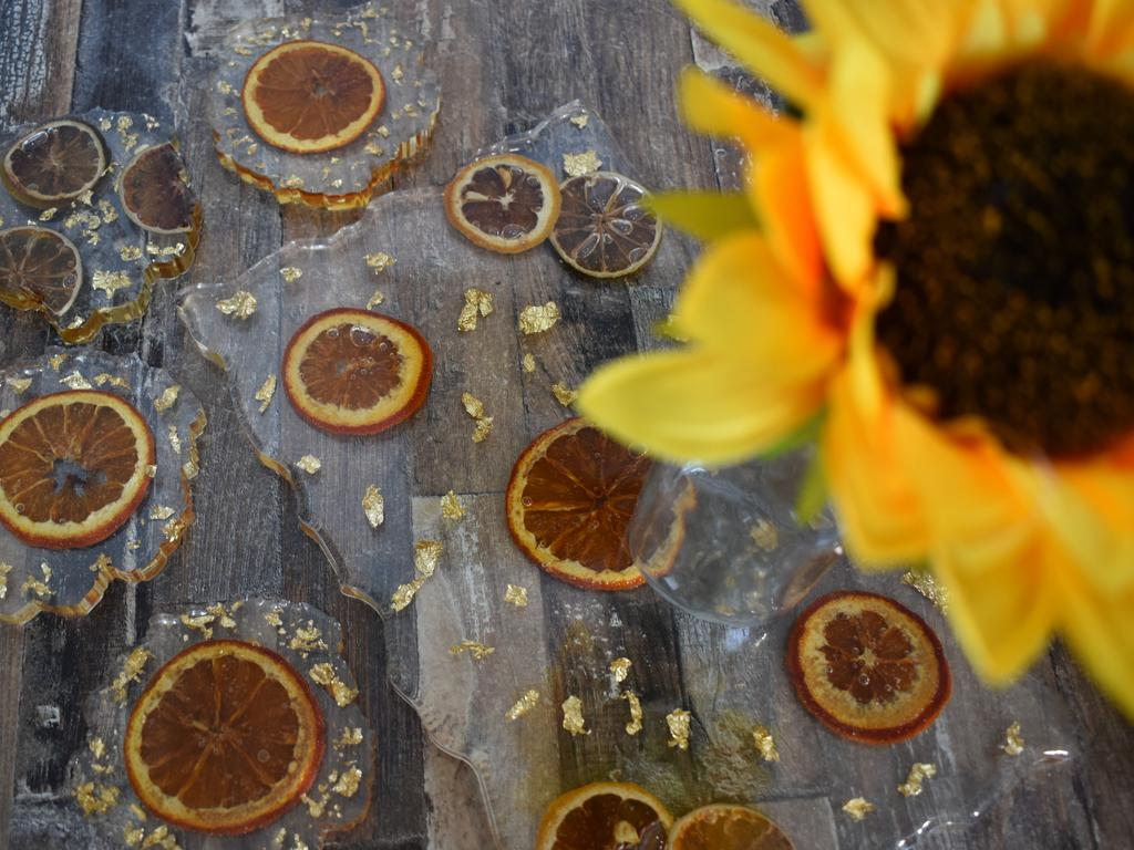 DRIED FRUIT: Using orange and lime wheels, which Bundy local Nadine Chessell dries herself, she has created stunning placeboards and matching coasters. Picture: Rhylea Millar.
