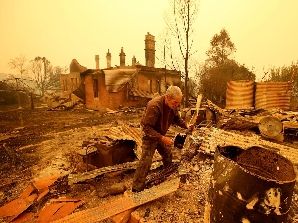 Malcolm Elmslie sifts through the remnants of his house in Cobargo after a firestorm swept through the area on New Year's Eve. Picture: Stuart McEvoy