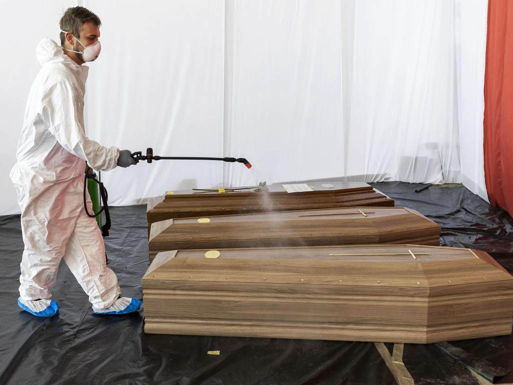Funeral homes around the world have been taking precautions during the pandemic. Here a man sanitises the coffin of a victim of COVID-19 in Italy. Picture: Marco Di Lauro/Getty Images