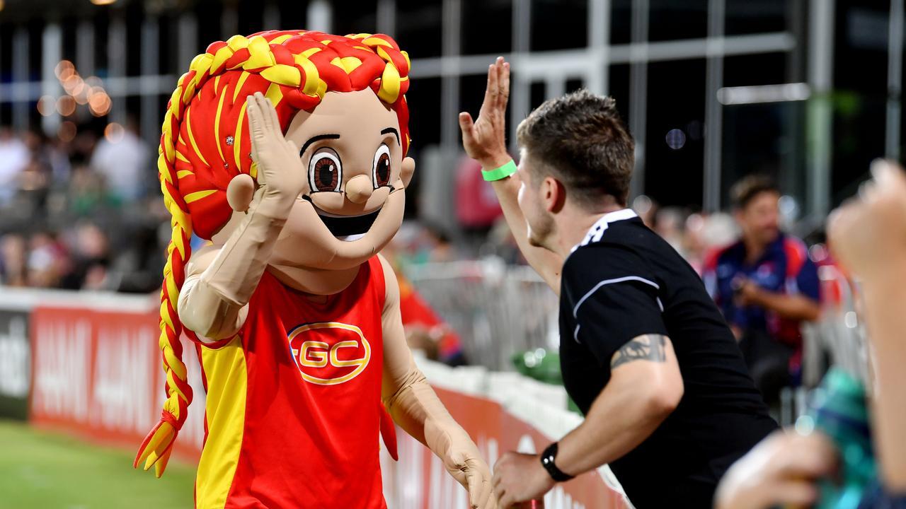 A fan high fives the Gold Coast Suns AFLW mascot at the Gold Coast Suns AFLW and Geelong Cats at Harrup Park. Picture: Tony Martin