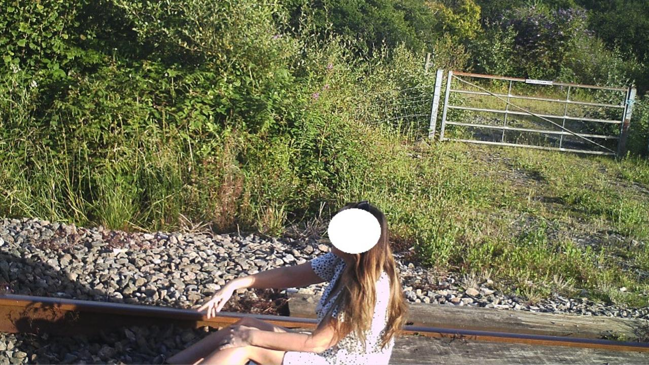 One image shows a woman wearing a dress sitting between a track as she poses for a photo. Picture: Twitter/NetworkRail