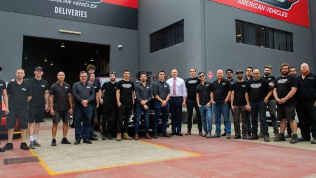 Peter Dutton pictured with staff at SCD American Vehicles.