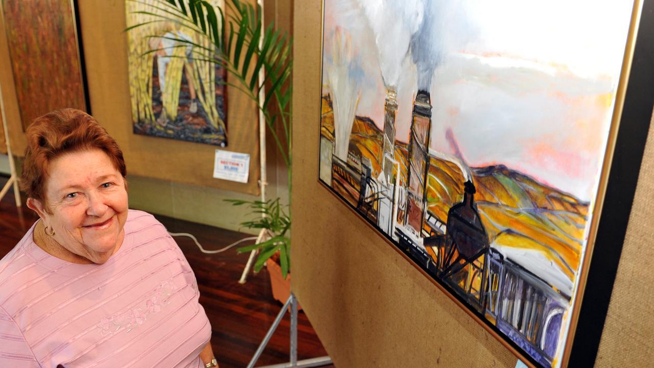 Secretary of the Bundaberg Arts Festival Association, Merle Beran, alongside the award-winning painting by Jennifer Mc Duff titled