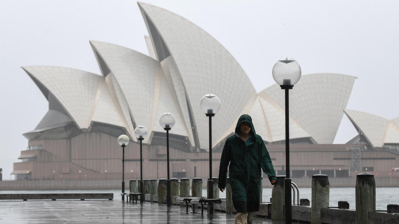 A man braves the wet weather near the Sydney Opera House. Picture: NCA NewsWire/Bianca De Marchi