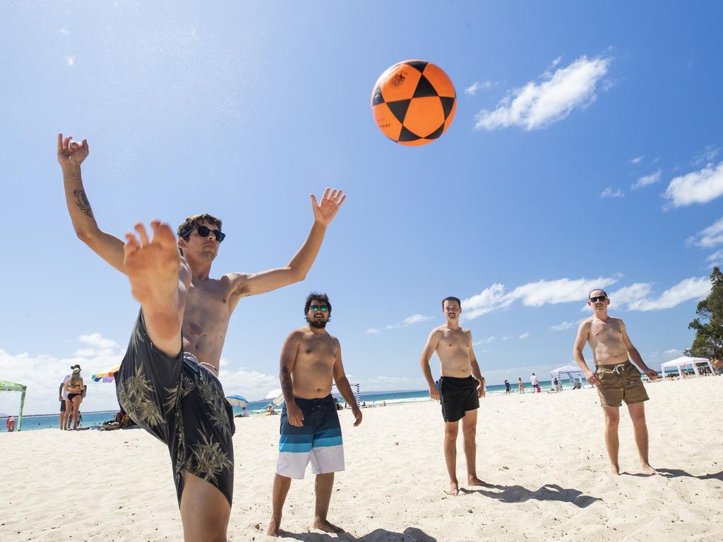 Backpacker Jackson Silva, 25, playing football with his friends at Noosa Main Beach. Photo: Lachie Millard