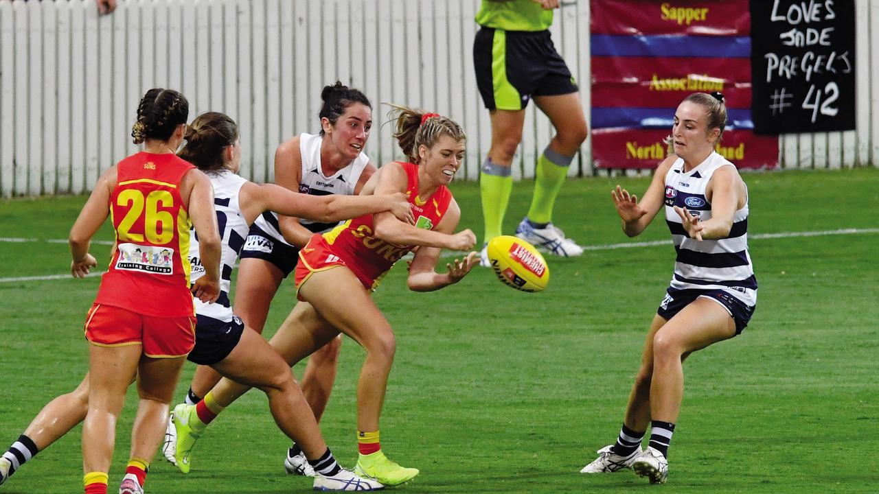 Gold Coast Suns AFLW player Kalinda Howarth handballs while surrounded by Geelong Cats players at Harrup Park. Picture: Tony Martin