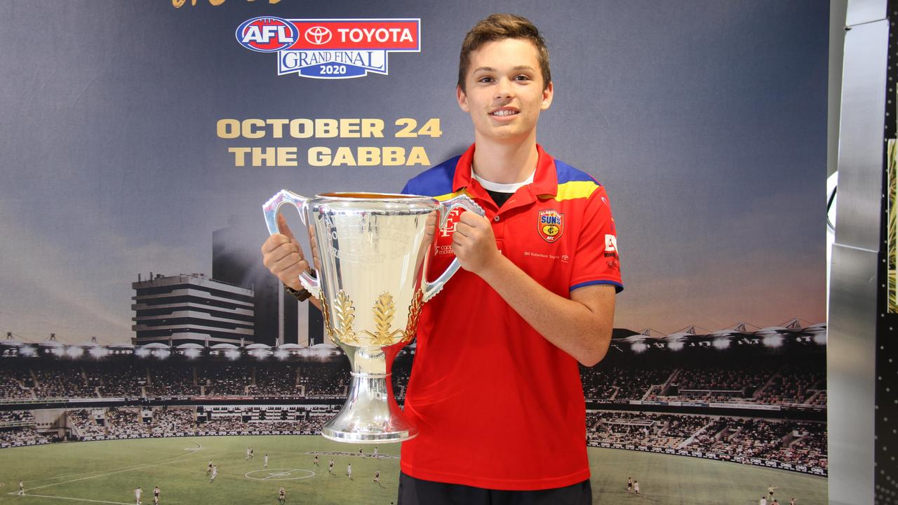 Gladstone Suns player Callum Hope, 14, holds the Toyota AFL Premiership Cup at Bill Robertson Toyota during a regional promotional tour. Picture Rodney Stevens