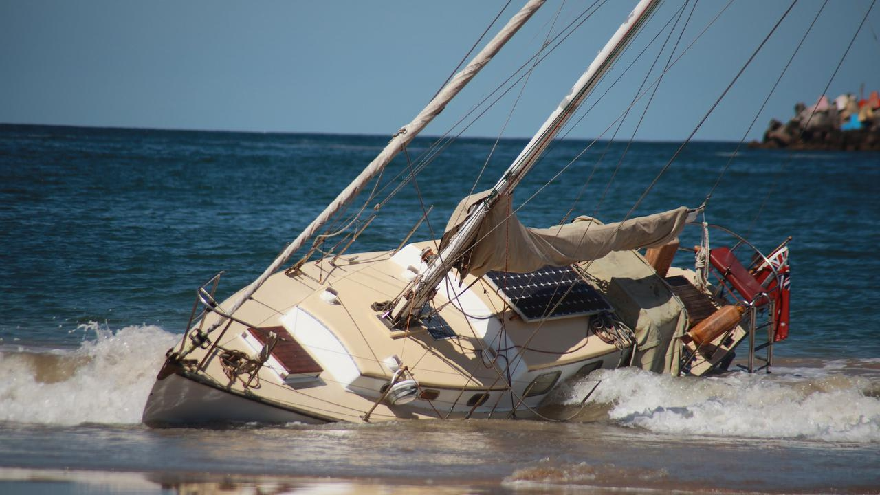 A yacht washes up on Jetty Beach. Photo: Frank Redward