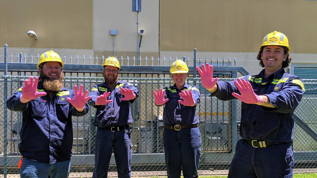 Gladstone Ports Corporation employees wearing pink gloves to raise awareness for Breast Cancer Awareness Month.