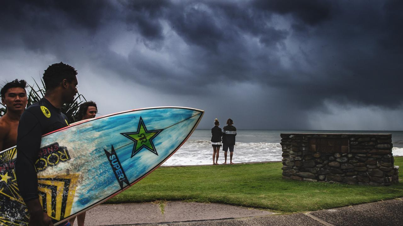 Rain squall passes over surfers at Alexandra Headland as wet weather sets in on the Sunshine Coast. Photo: Lachie Millard