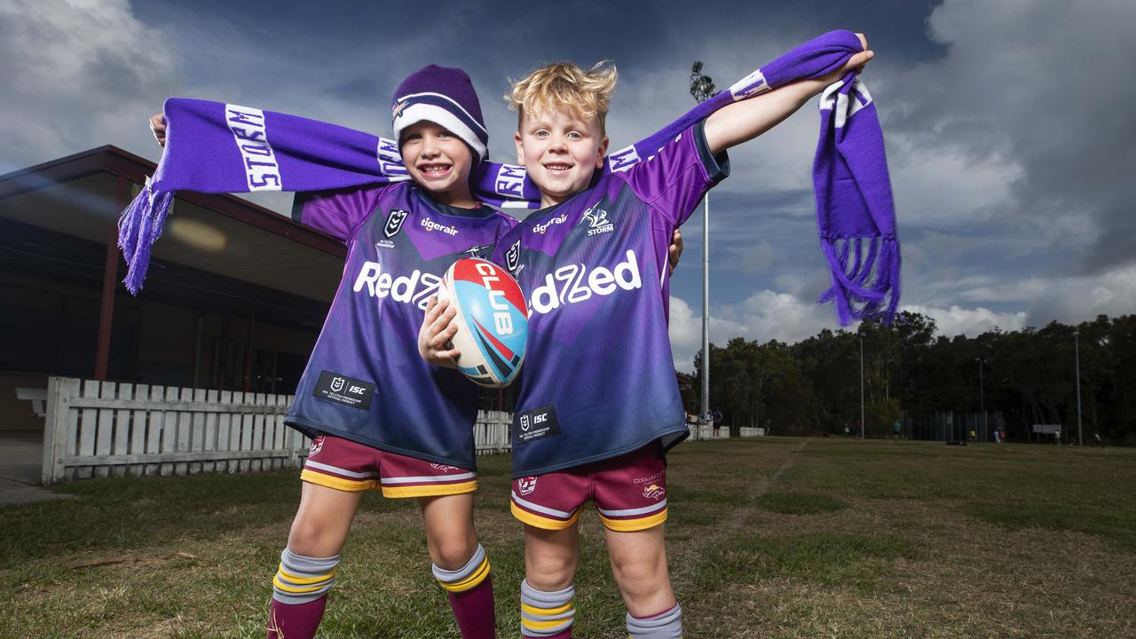 With storms rolling through in the back ground, two Melbourne Storm fans don the team's jersey ahead of their clash with Penrith Panthers on Sunday. Photo Lachie Millard