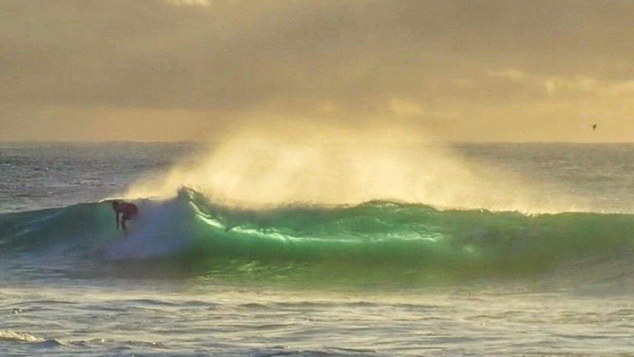 A surfer takes off at Main Beach, Nambucca.
