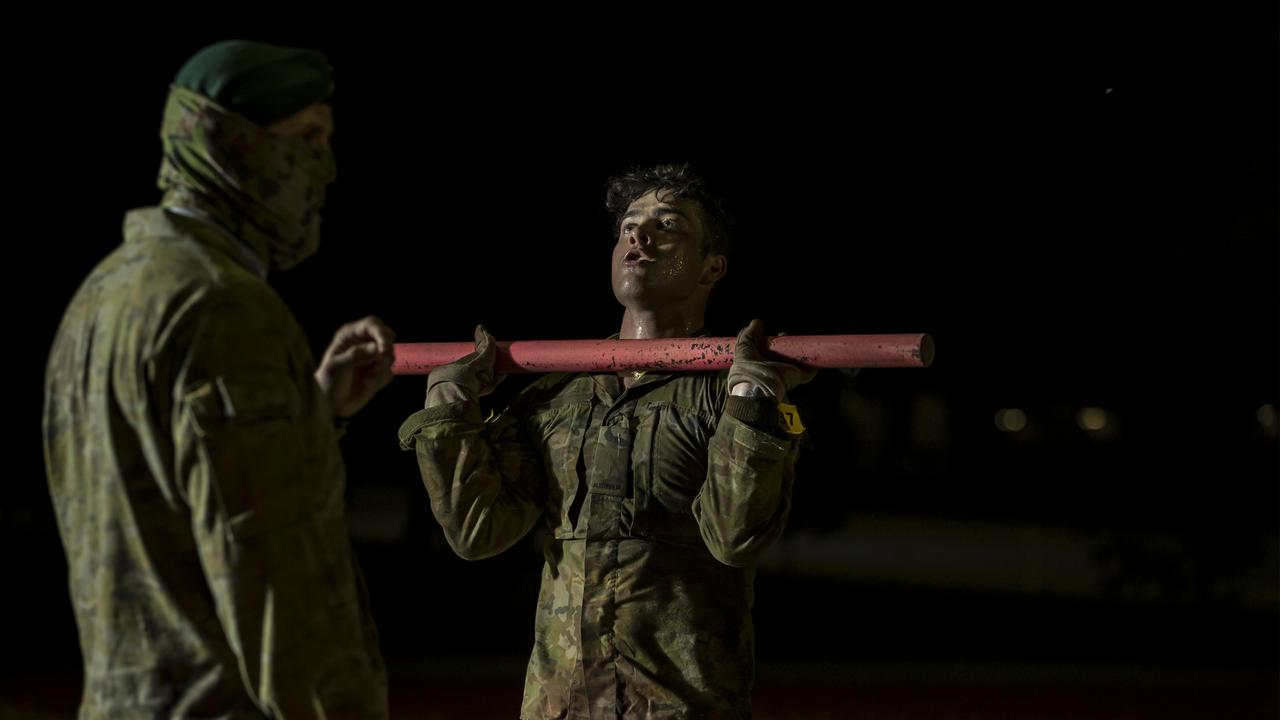 An Australian Army special forces soldier (left) supervises Commando candidates during an early morning physical training session.
