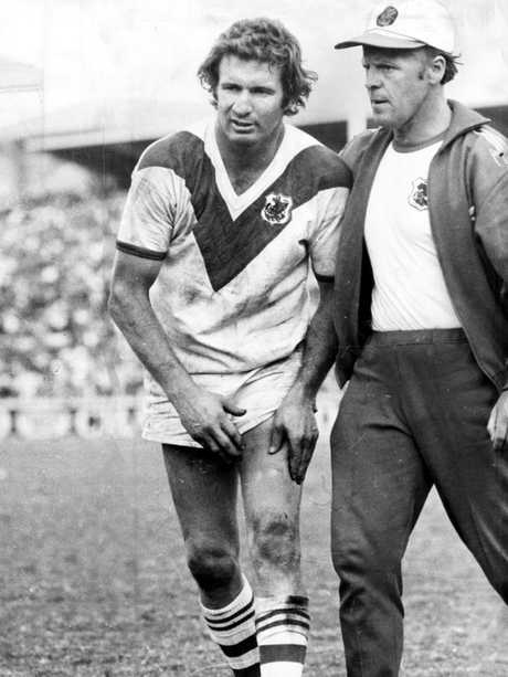 Graeme Langlands is assisted from the field during the 1975 grand final.