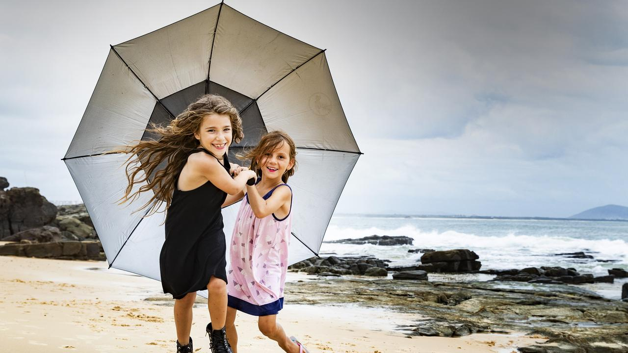 7-year-old best friends Lexi White and Summer Kelly brave the wet weather at Mooloolaba in February. Photo: Lachie Millard