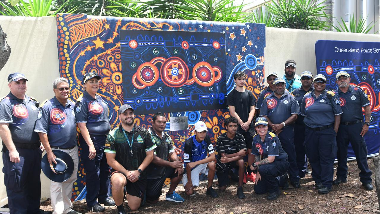 Darumbal artists pose with Police Liaison Officers in front of the Look to the Stars mural