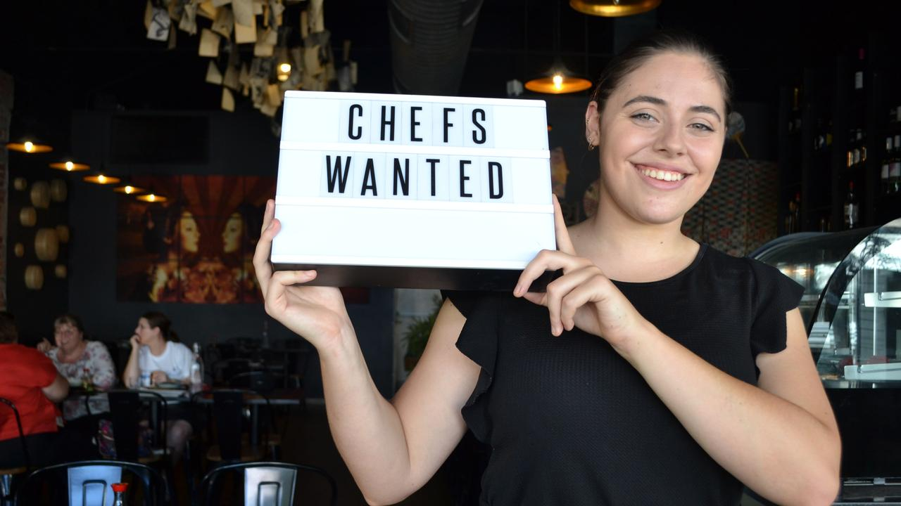 Hannah Cifuentes holds up a 'chefs wanted' sign.