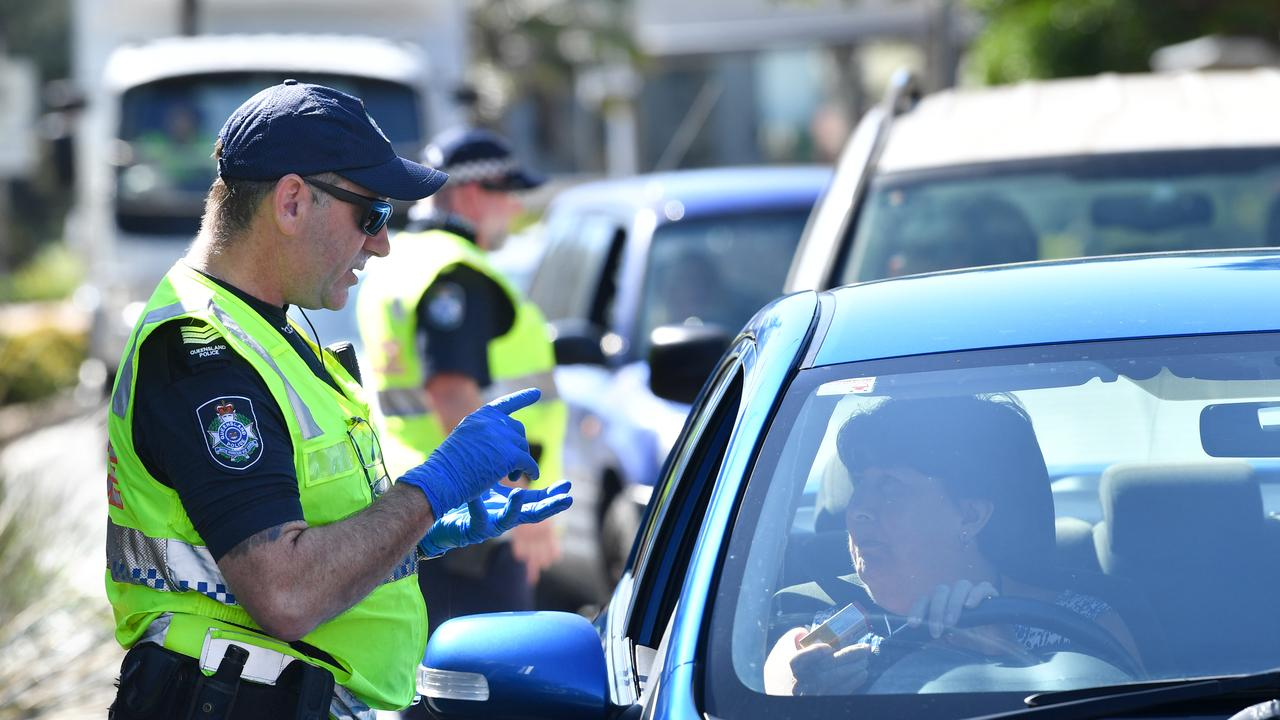 Police are seen stopping cars at a check point on the Queensland and New South Wales border on Griffith Street in Coolangatta at the Gold Coast. (AAP Image/Darren England).