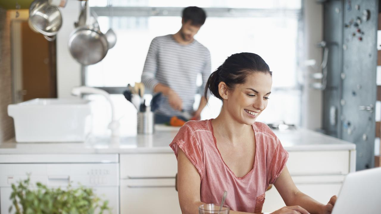Generic shot of woman working on her laptop in the kitchen. Today's kitchens are more than just a food-prep zone, and have become spaces where we work and socialise. Free to use from iStock
