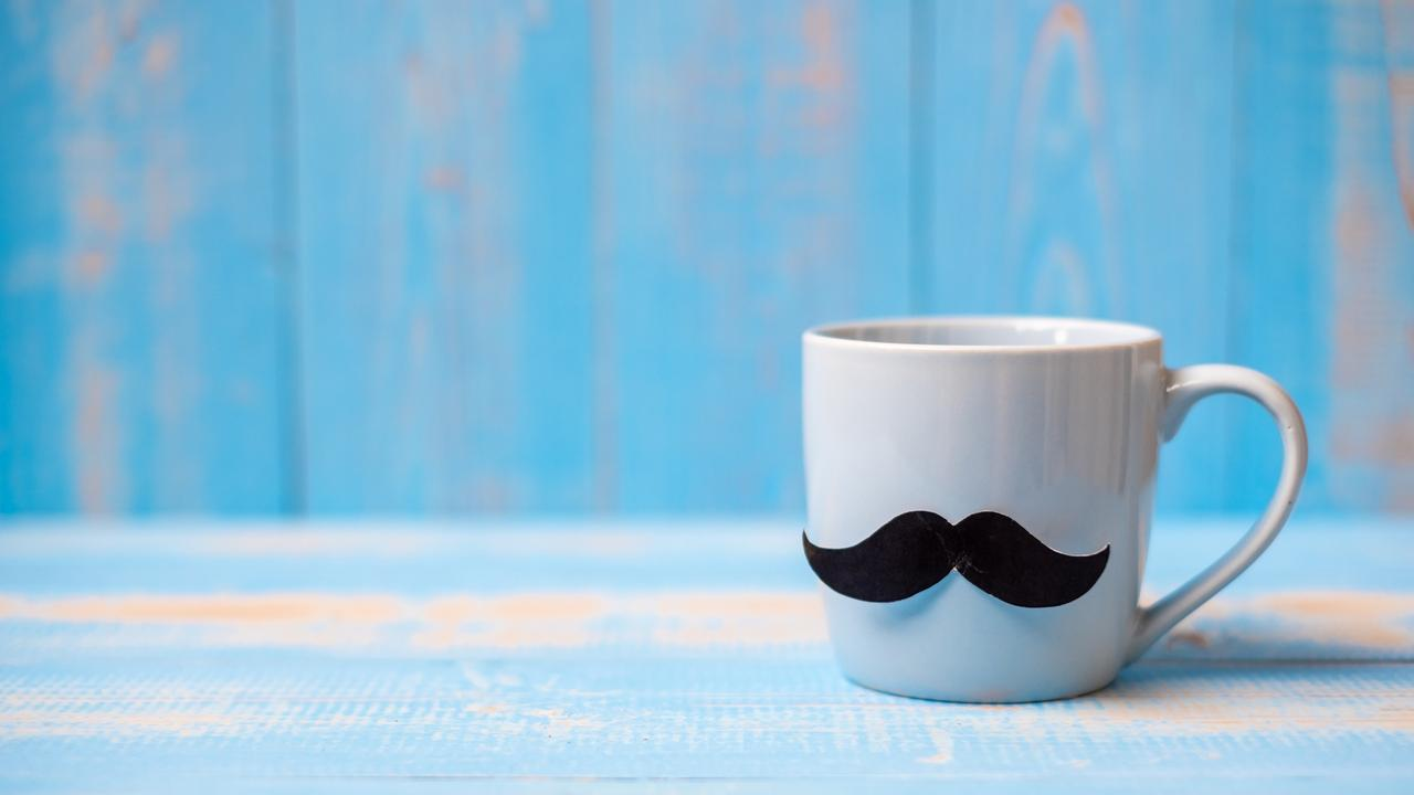 Blue coffee cup with Black mustache on wood table background in the morning. Father, International men day, Prostate Cancer Awareness and World cancer day concept