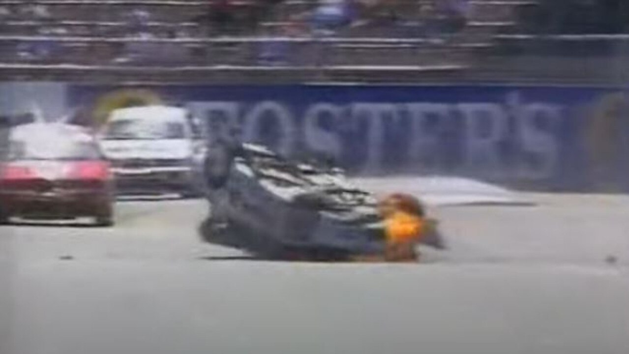 His car which is on fire skids back into the middle of the track.