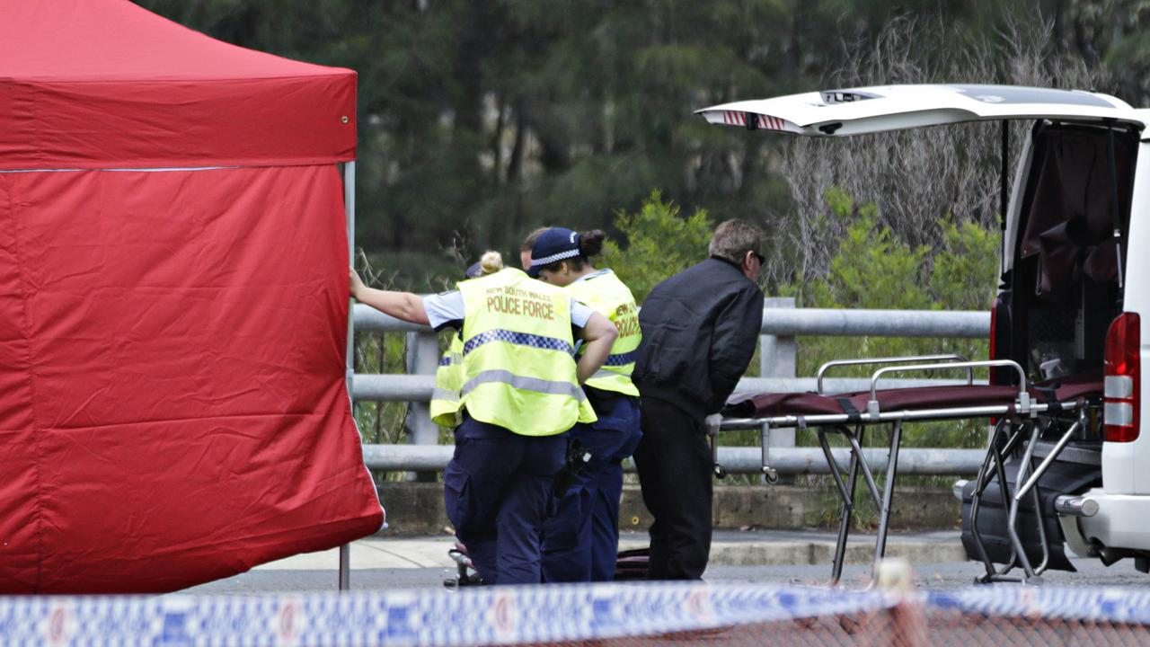A tent provides privacy and rain cover as the coroner's team collect the bodies of the men. Picture: Adam Yip/ Second Story