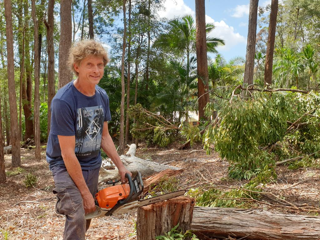 Dean Rd resident Reijo Pesu cleans up after Saturday night's freak storm which felled trees in his Doonan property.