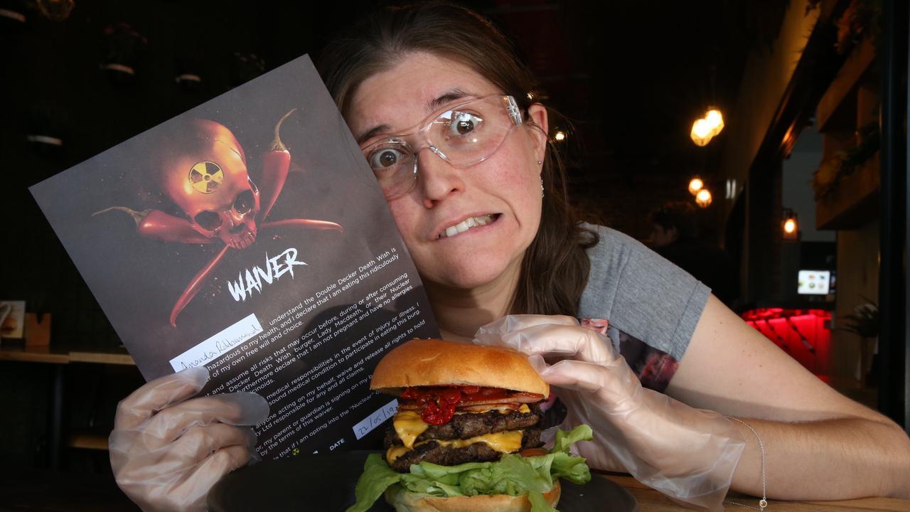 Journalist Amanda Robbemond attempts to eat Australia's hottest burger at Burger Urge, and fails miserably. Picture Glenn Hampson