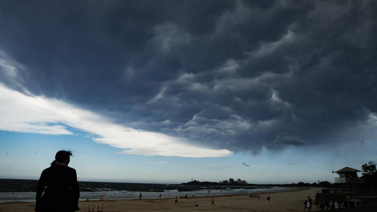 A young girl watches as a storm front passes over Mooloolaba Beach on Saturday. Picture: Lachie Millard