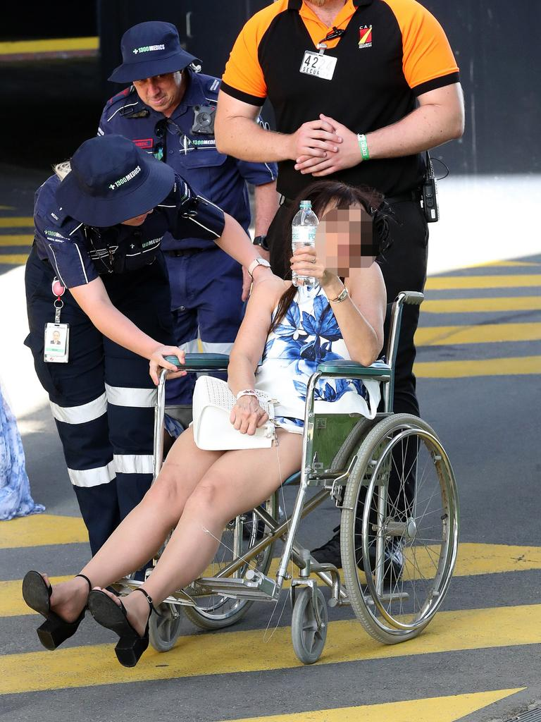 A woman too intoxicated to walk is put in a wheelchair and assisted by medics. Photographer: Liam Kidston