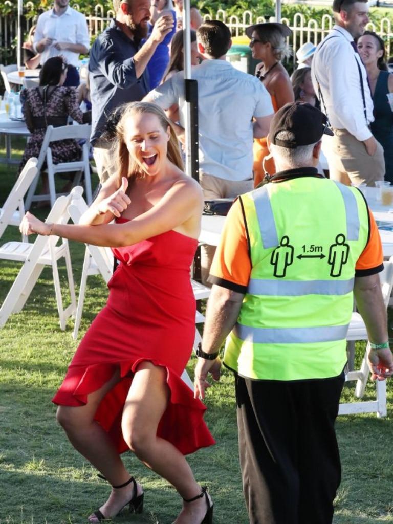 A woman dances in front of social distancing enforcement security.