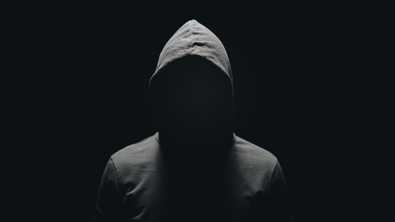 faceless man in hoodie standing isolated on black