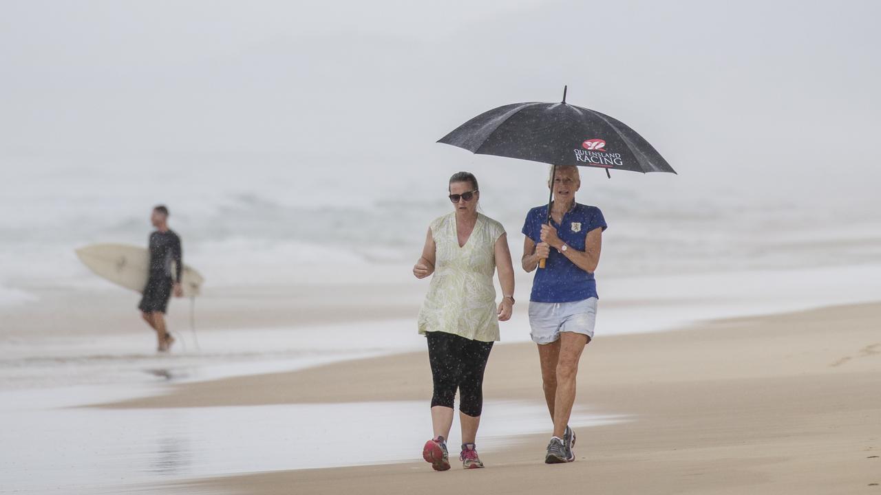 Beachgoers brave wet weather at Sunshine Beach during the holidays. Photo: Lachie Millard