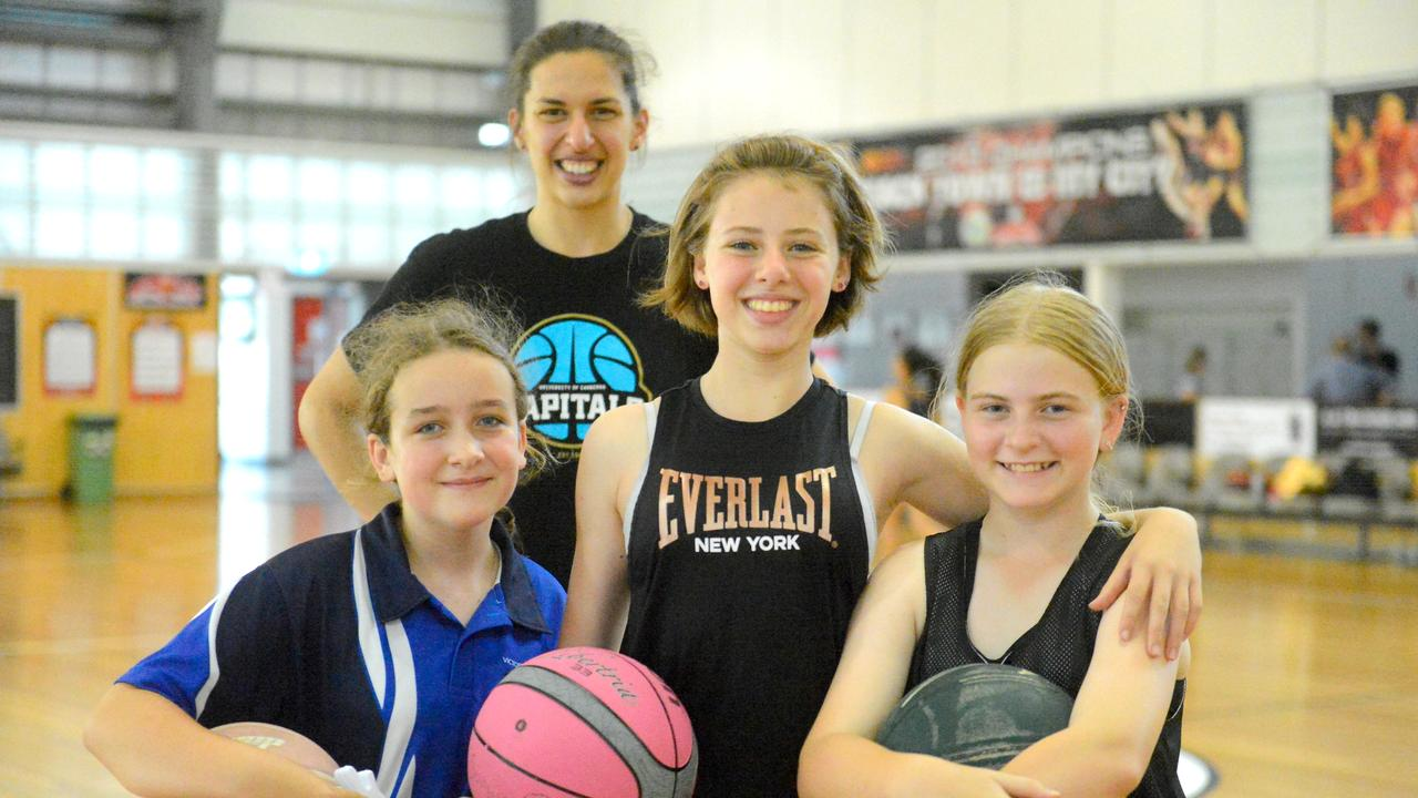 Canberra Capitals star Marianna Tolo with young fans (from left) Amity Simpson, 11, Sophie Van Essen, 11 and Indie Goodworth, 11, at the open clinic at Mackay Basketball Stadium on Thursday.