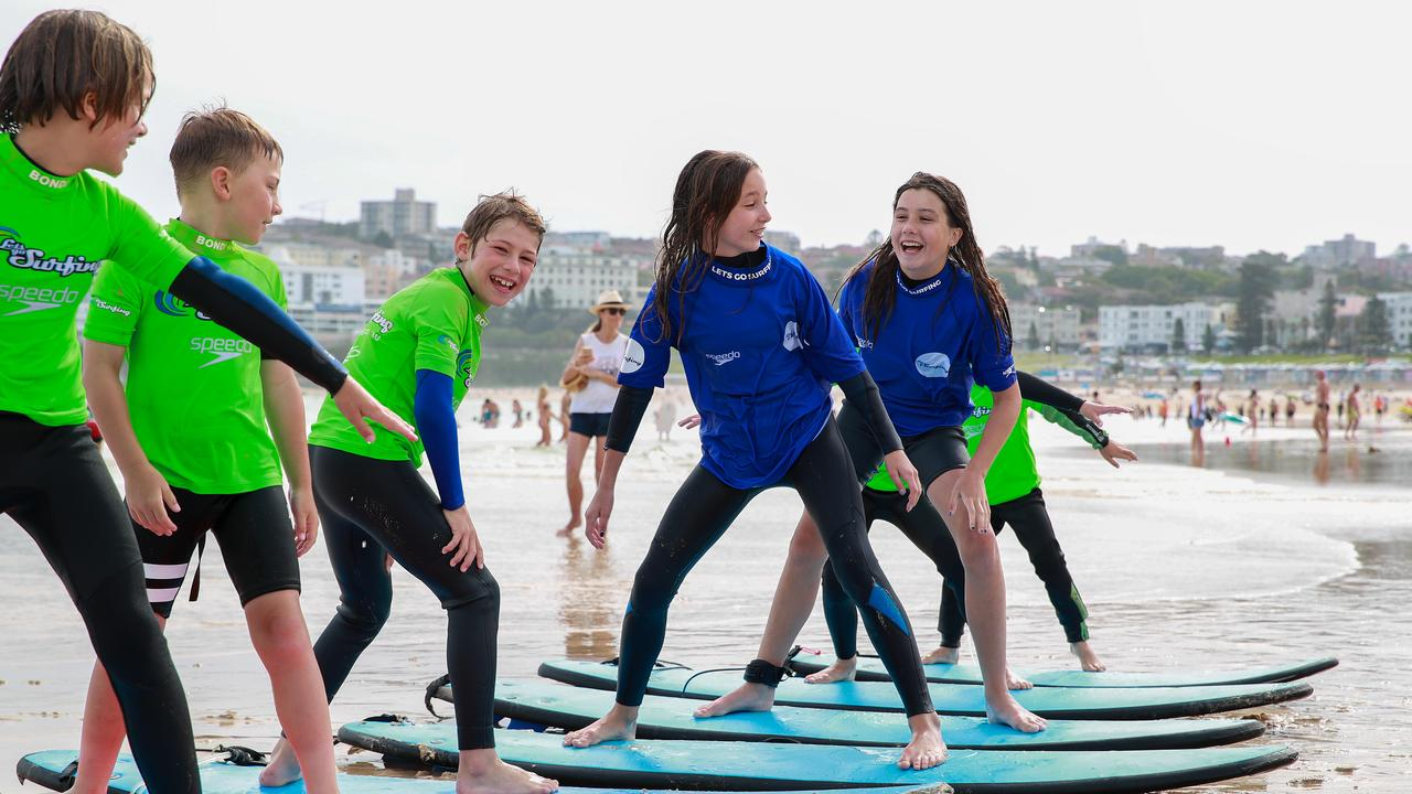 Noah Minten-Super, Ander Fletcher Zaballa & Camille Gabrynowicz enjoying the Let's Go Surfing class at Bondi Beach. The government is planning to offer $25 vouchers for recreation, dining & entertainment in the State Budget. Picture: Justin Lloyd