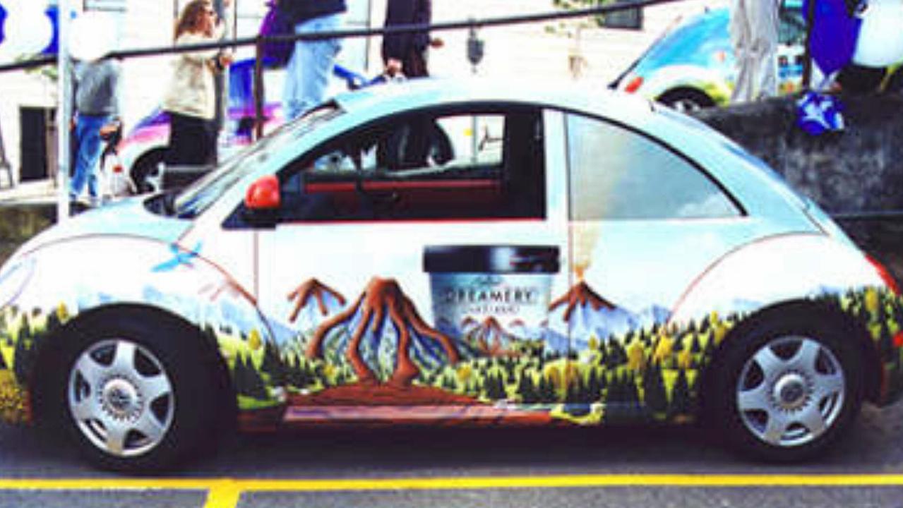Motor vehicle displaying advertising car wrap.