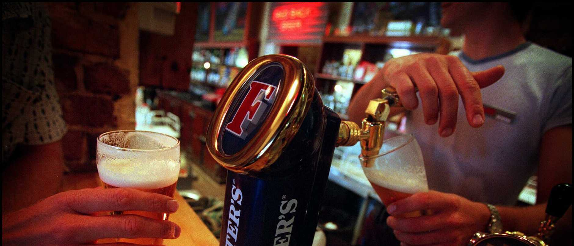 Barmaid pouring schooner of Foster's beer from tap at Perth's Queens Tavern. /Alcohol / Glass  /WA / Hotels   froth logo logos hands generic pub bar pulling glass
