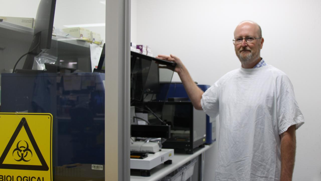 ROBOTIC DIAGNOSTIC: NSW Health Pathology Supervising scientist Glenn Hawkins with a High Plex robot which allowed his team of laboratory scientists to process more than 50,000 of the regions 80,000 COVID-19 tests samples. Photo: Alison Paterson
