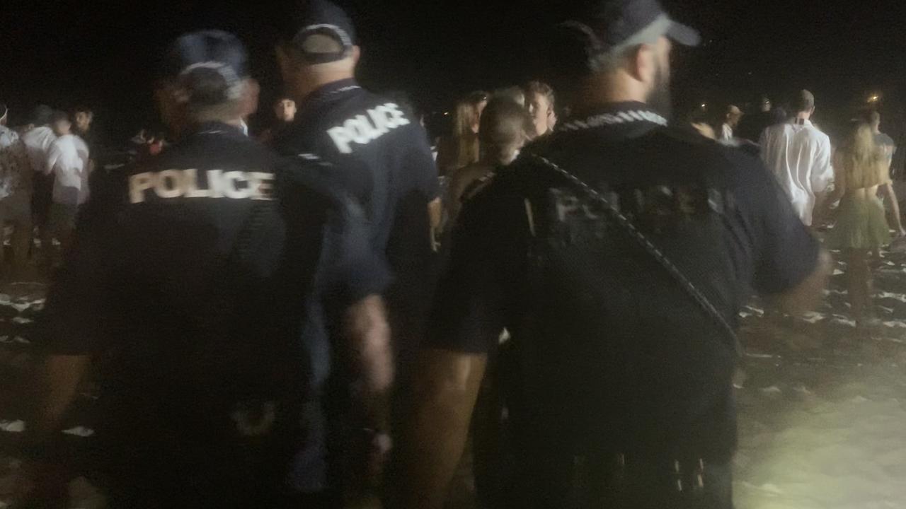 Police patrol Noosa Main Beach during huge schoolies' gathering.