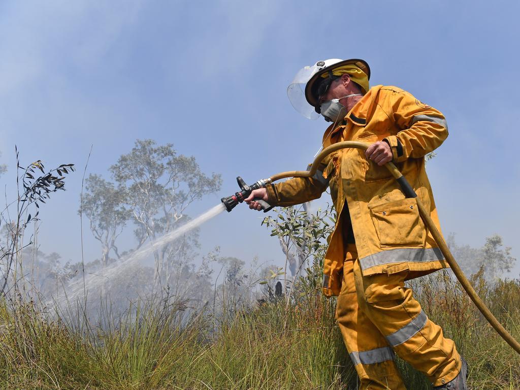 A firey battling a blaze at Noosa North Shore. Photo Patrick Woods / Sunshine Coast Daily.