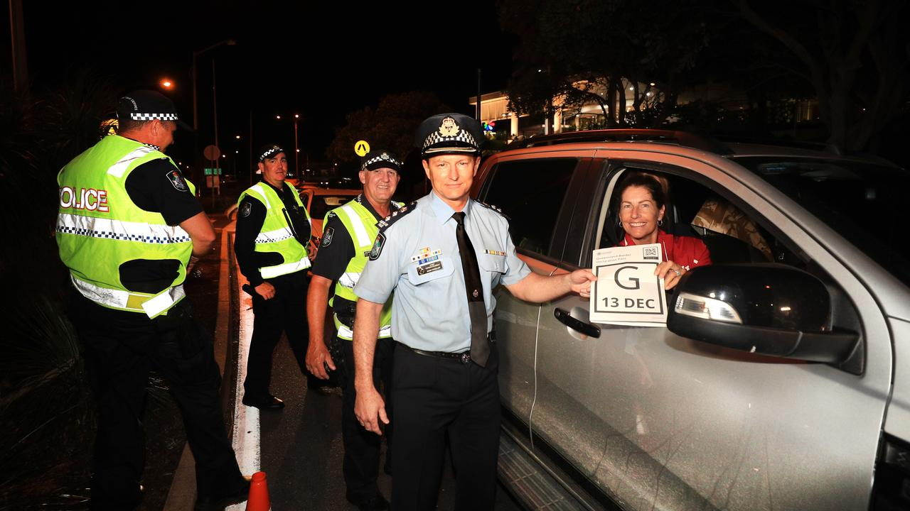 Queensland Police Superintendent Mark Wheeler takes back a QLD Border pass and welcomes Wendy Van den Akker as the first vehicle back into the state after border restrictions were lifted at 1am. Picture: Scott Powick