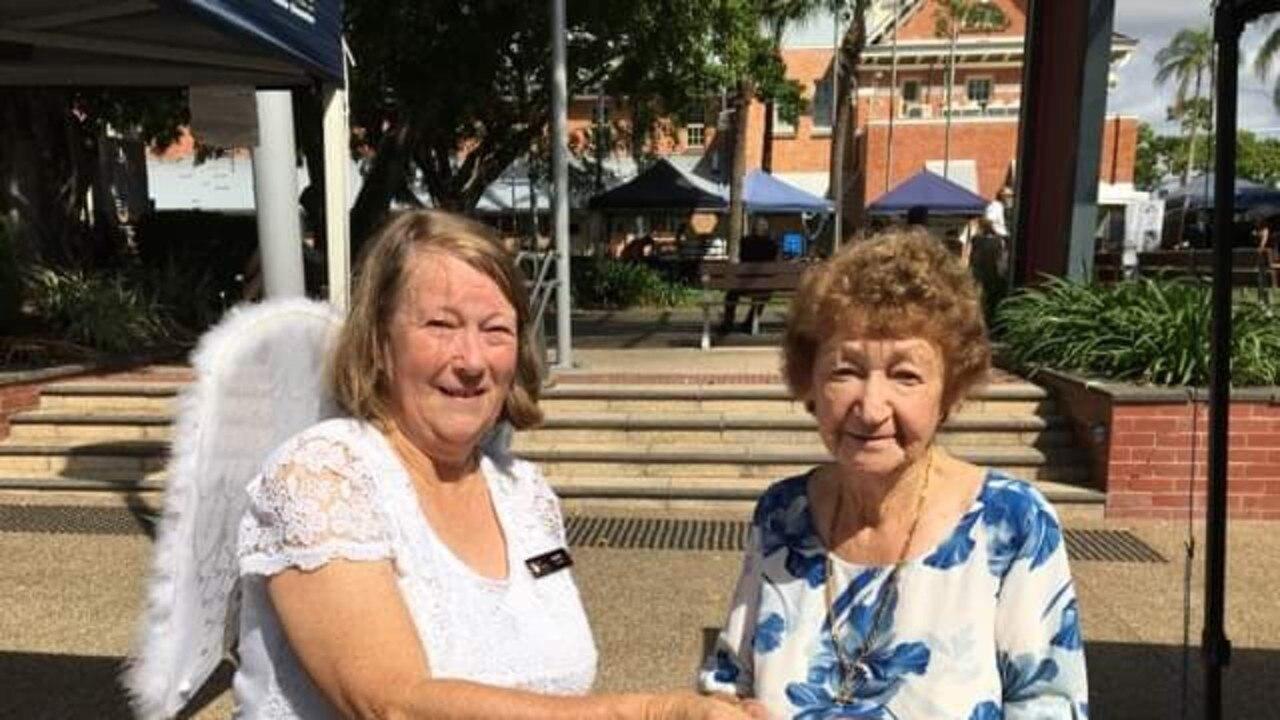 Regular market goer Joyce makes a donation to winged angel committee secretary Nan Ott.